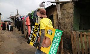A man carries an ANC campaign poster through Alexandra township in Johannesburg