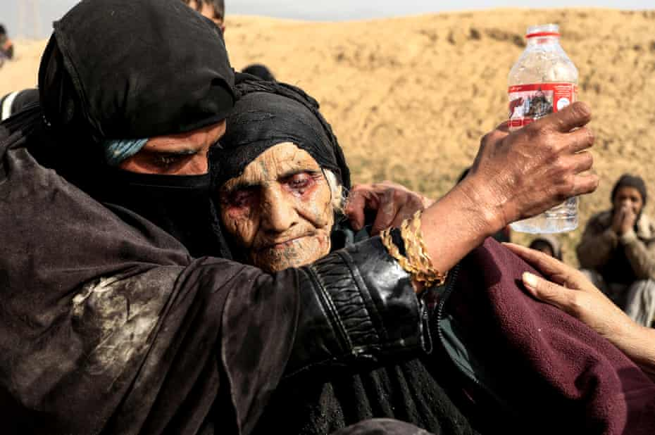Displaced women wait to be transported while Iraqi forces battle against Isis in western Mosul, on 27 February