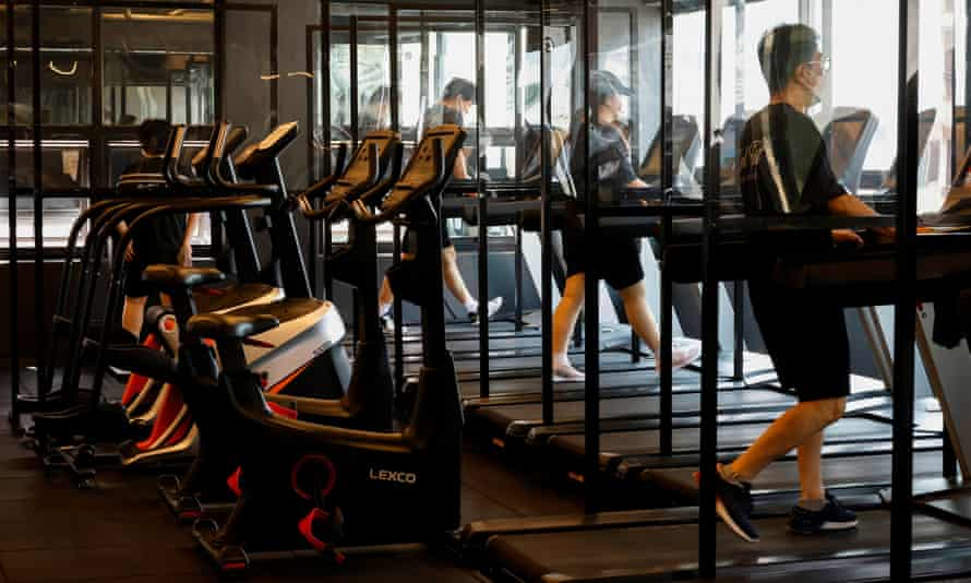 Gym members use a treadmill at a fitness club in Seoul