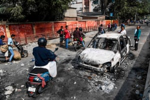 Guwahati, India. Commuters drive past gutted vehicles, a day after protests against the government's citizenship amendment bill