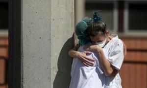 Medical wokers hug each other outside the emergency rooms at Severo Ochoa hospital in Leganes, Spain.
