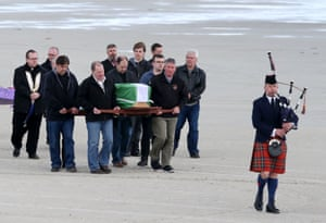 Mourners carry the coffin of Eilidh MacLeod, which is draped with the Barra flag, across Traigh Mhor beach after the body of the 14 year-old was flown home ahead of her funeral.