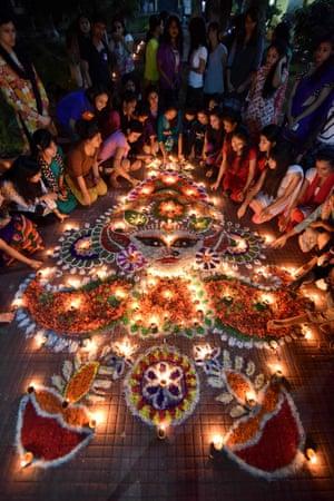 Indian girls light earthen lamps