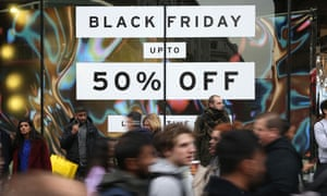 Shoppers pass a sign for a Black Friday sales event on Oxford Street, London, on 24 November 2017
