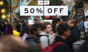 Shoppers pass a promotional sign for 'Black Friday' sales discounts on Oxford Street in London