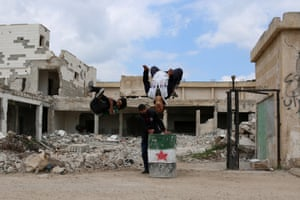 Parkour coach Ibrahim al-Kadiri (L), 19, and Muhannad al-Kadiri, 18, demonstrate their parkour skills over a bin painted with an opposition flag in the rebel-held city of Inkhil, west of Deraa
