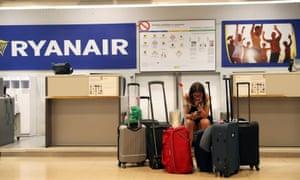 A stranded Ryanair passenger in Madrid checks her phone