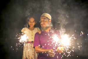 A man and his daughter hold firecrackers