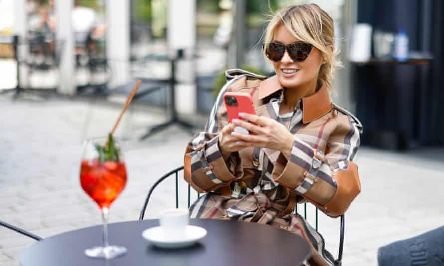 Woman sits at cafe table wearing Burberry trenchcoat while looking at mobile phone