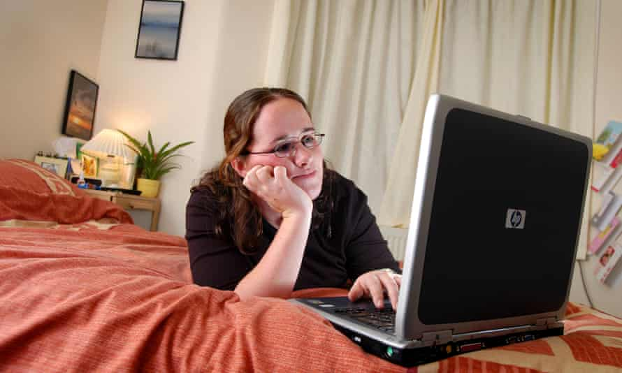 young woman with laptop in on bed