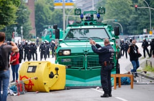 An officer stands in front of a barricade made by protesters to block a police vehicle