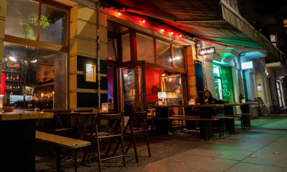 Two people sit outside a bar in Berlin