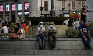 People sit by a fountain while wearing face masks in Madrid, Spain on September 16 2020