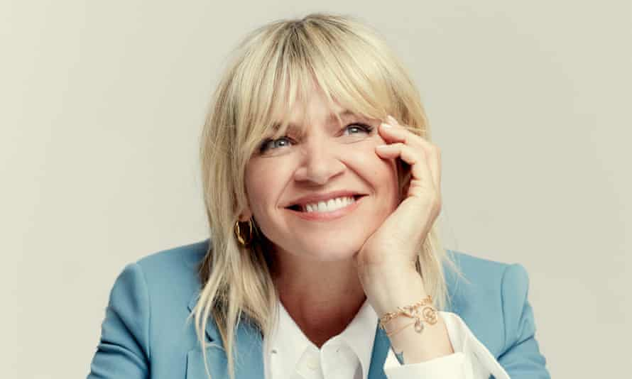 Zoe Ball, smiling, face resting in her hand