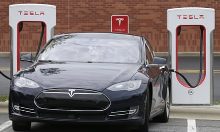A Tesla car recharges at a charging station at Cochran Commons shopping center in Charlotte, N.C.