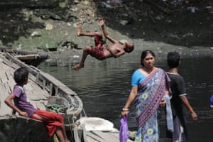 Kolkata, India. A boy dives into the polluted Adi Ganga river to collect coins thrown there by devotees visiting the Kalighat temple. At least 100 boys earn their income in this way