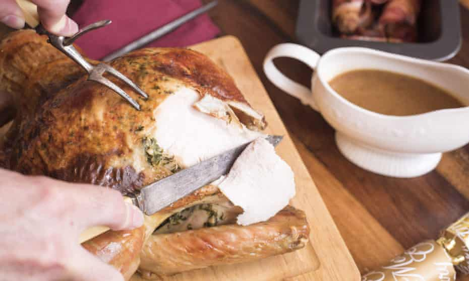 Man carving the Christmas turkey with a carving knife and fork at the table with a gravy boat and roast potatoes alongside