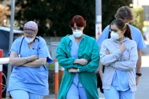 Health workers wear protective face masks outside a hospital in Padua, Veneto region, northern Italy