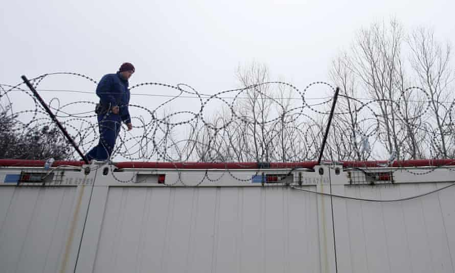 A Hungarian police officer stands guard at the border with Serbia near a camp for migrants.