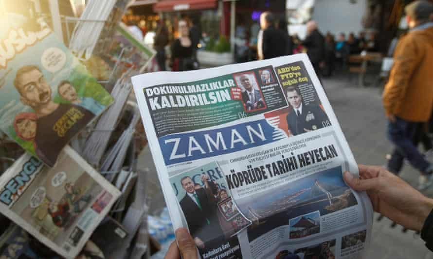 A man reads a copy of Zaman newspaper