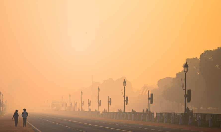 Two men walk along Rajpath amid smoggy conditions in New Delhi last month.