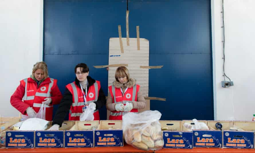 Volunteer Red Cross workers arrange food packs to be distributed to refugees at a transit centre in Croatia