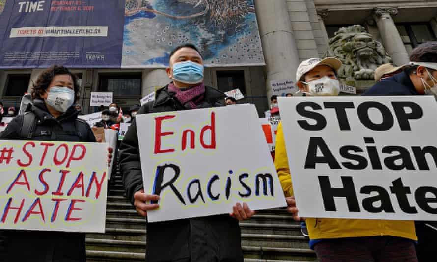 People hold signs at a Stop Asian Hate rally in Vancouver.