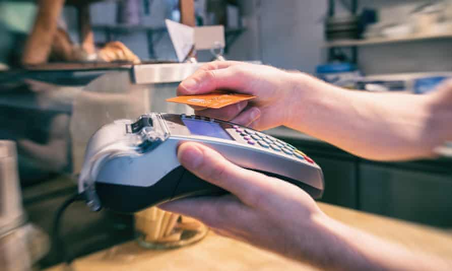 Close up of a hand using a contactless credit card terminal to pay