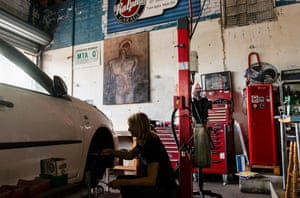 a mechanic works one a car in front of a painting