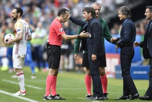 Referee Cuneyt Cakir talks to Antonio Conte after Conte thumped the ball away.