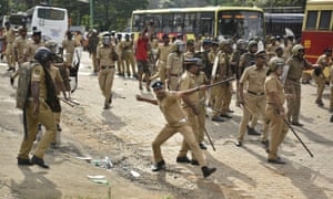 A police officer hurls back a stone at a protester at clashes outside the Sabarimala temple.