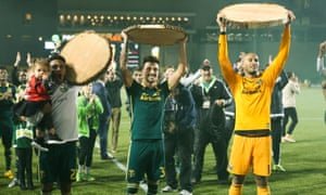 Assorted Portland Timbers players hold up the presentational log slices they won in a match against Kansas City. Yes, log slices.