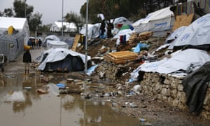 A refugee stands next to a pool of mud at Moria refugee camp on the eastern Greek island of Lesbos