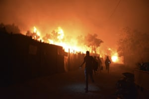 Refugees and migrants run as fire burns in the Moria refugee camp on Lesbos on Wednesday.