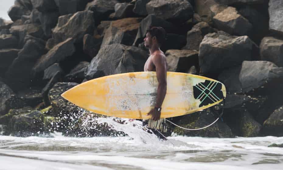 Raghul Paneerselvam, a surf champion, board shaper and repair master, heads into the water alongside a manmade breakwater in Mahabalipuram.