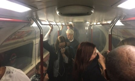 Passengers cover their faces as a carriage on a Bakerloo line train fills with smoke at Oxford Circus station in London.