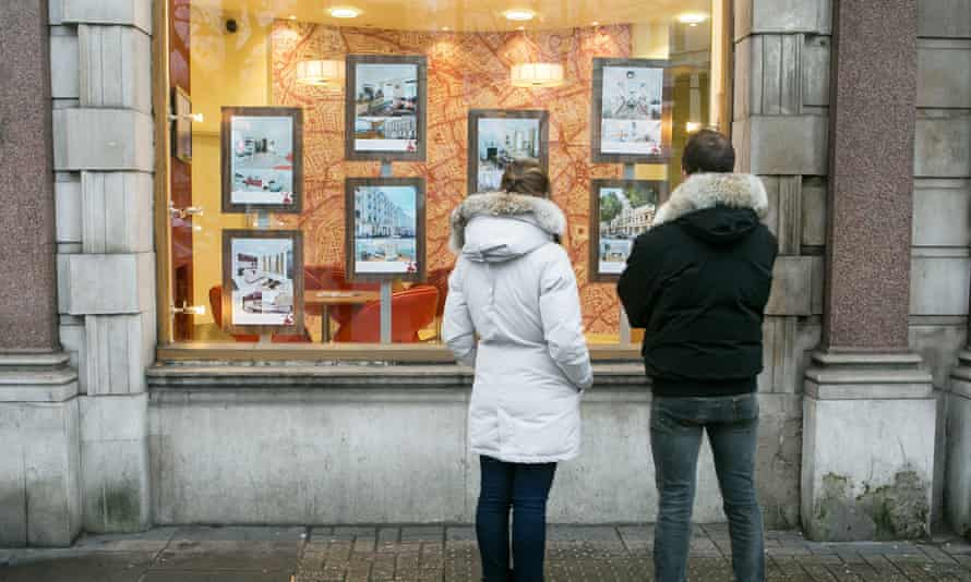 Couple looking in the window of an estate agents