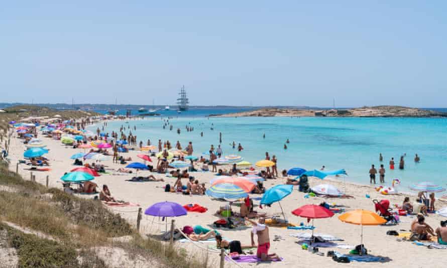 sunbathing on the Playa de Ses Illetes, Balearic Island of Formentera.