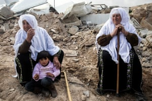 Miriam al-Shehadeh, aged 70, (right) sits in the rubble of her home
