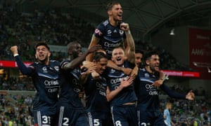 Mark Milligan celebrates with teammates after scoring the winner in the Melbourne derby.