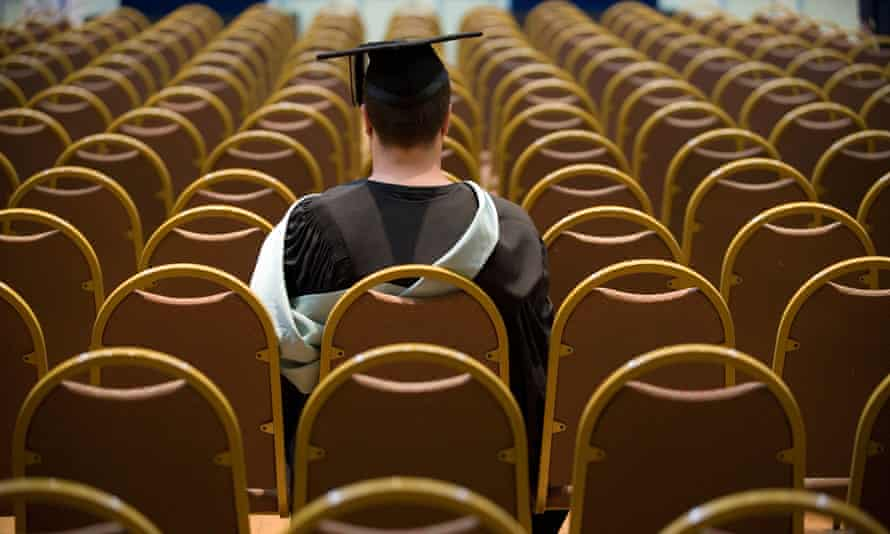 A graduate sitting alone waiting for ceremony to begin.