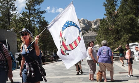 A Donald Trump supporter holding a QAnon flag visits Mount Rushmore national monument on 1 July 2020 in Keystone, South Dakota.