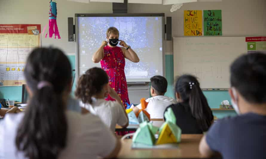 A teacher wears a mask at a school in Berlin as she explains new coronavirus rules to pupils