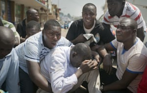 Opposition leader and presidential candidate Kizza Besigye is surrounded by his bodyguards after being overcome by teargas in Kampala, Uganda