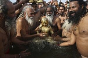 Followers of Shri Panchayati Naya Udasin Akhada give a ritualistic bath to their deity.