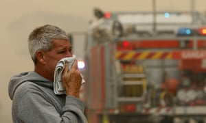 A resident watches the progress of bushfires near houses in Old Bar, NSW, on Saturday