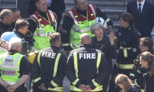 May speaks to members of the fire service as she visits Grenfell Tower