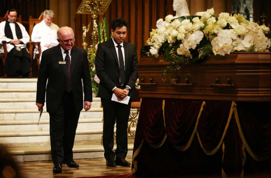 Alpha Cheng stands in front of his father's casket during his funeral service in October 2015.