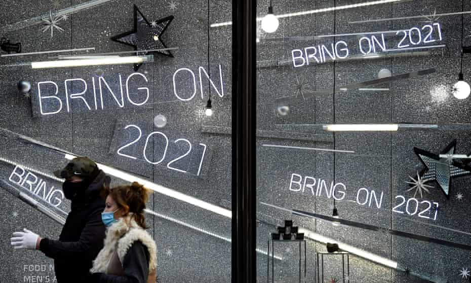 People wearing protective masks walk past a window display of a closed retail store in London.