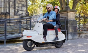 cezeta electric scooter on the streets of prague ridden by attractive young couple